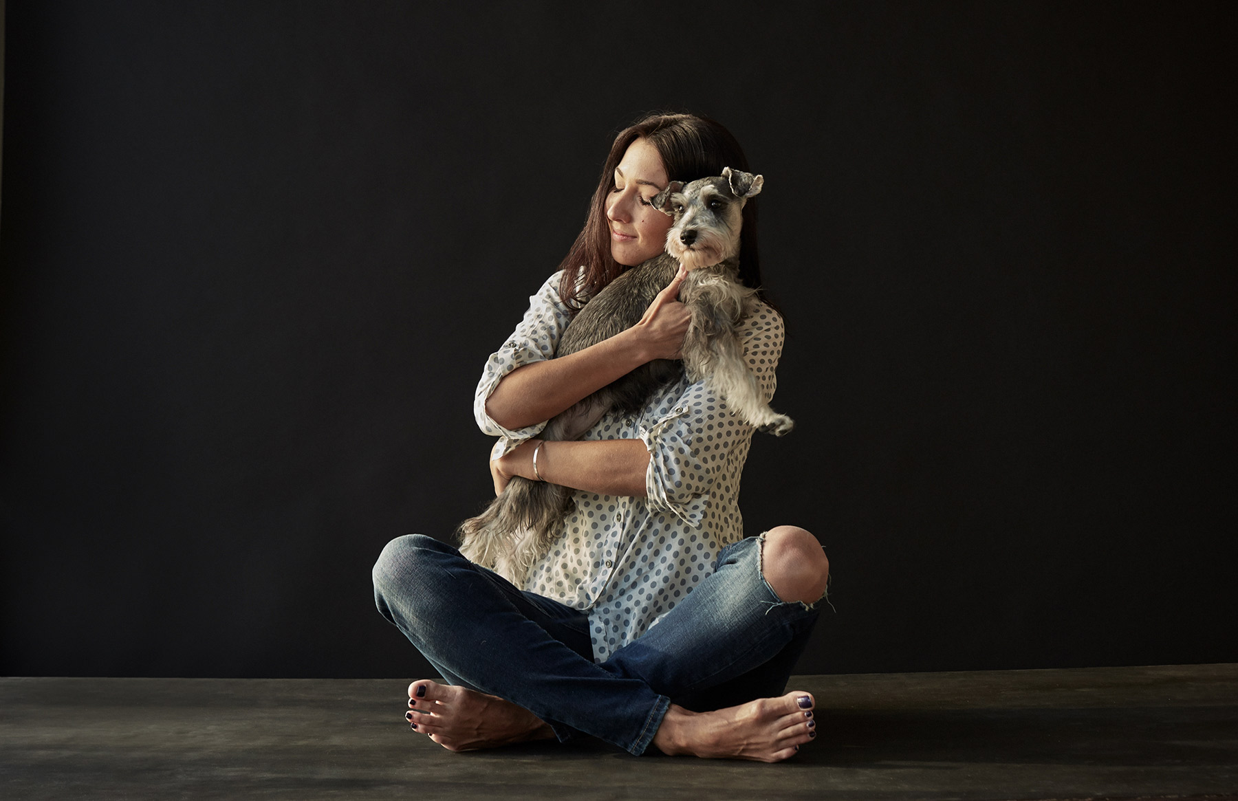 A-studio-portrait-of-a-woman-holding-a-Schnauzer-against-a-black-background