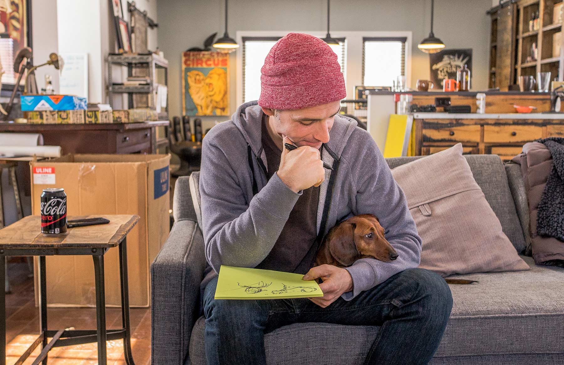 A-man-sketching-on-a-notepad-with-a-Dachshund-on-his-lap