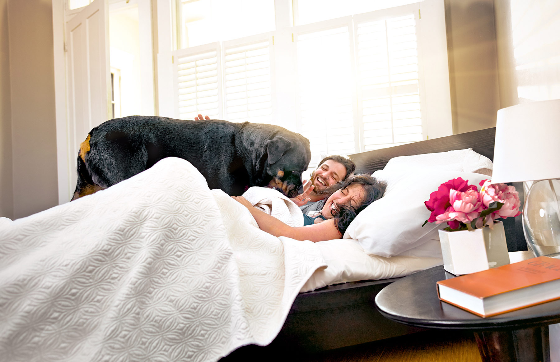 A-young-couple-in-bed-with-a-large-black-dog