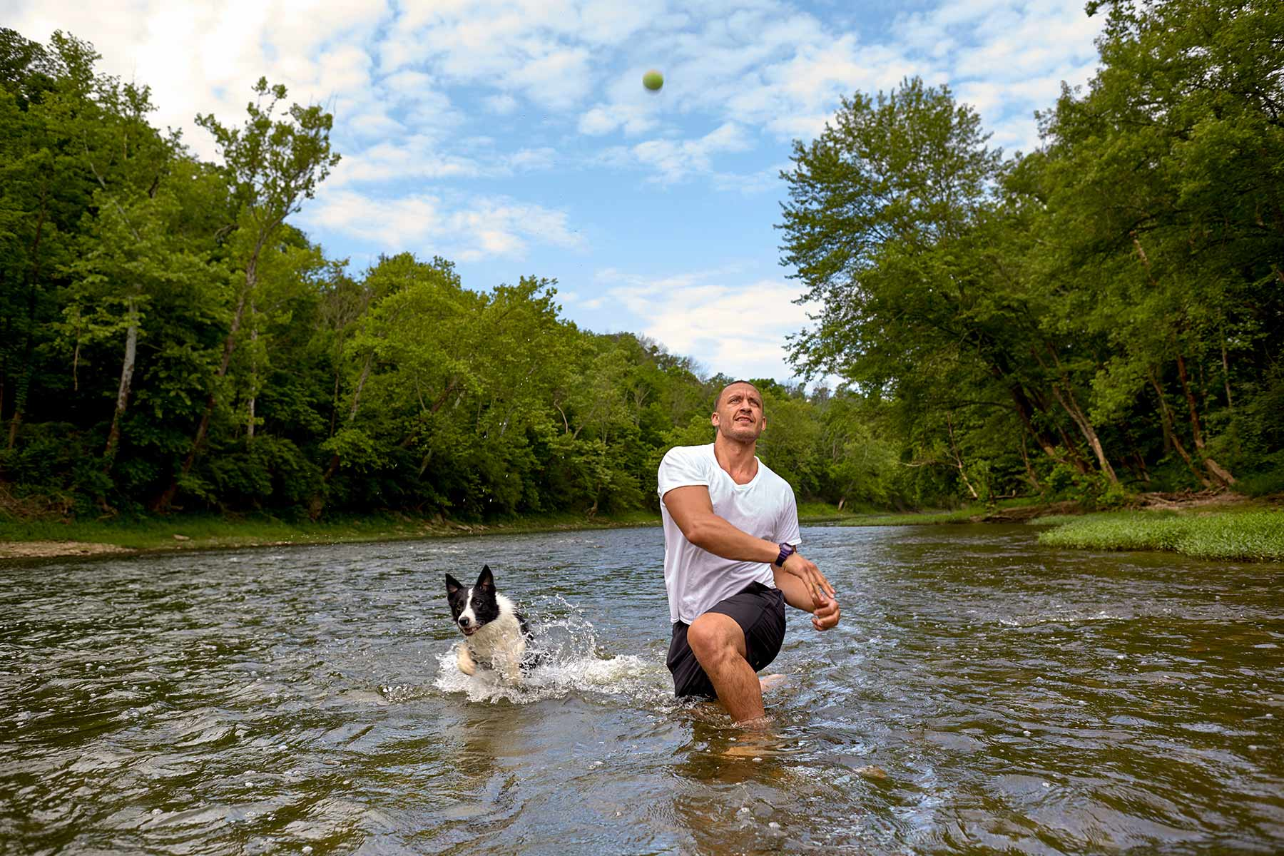 A-man-playing-fetch-with-his-dog-in-the-river