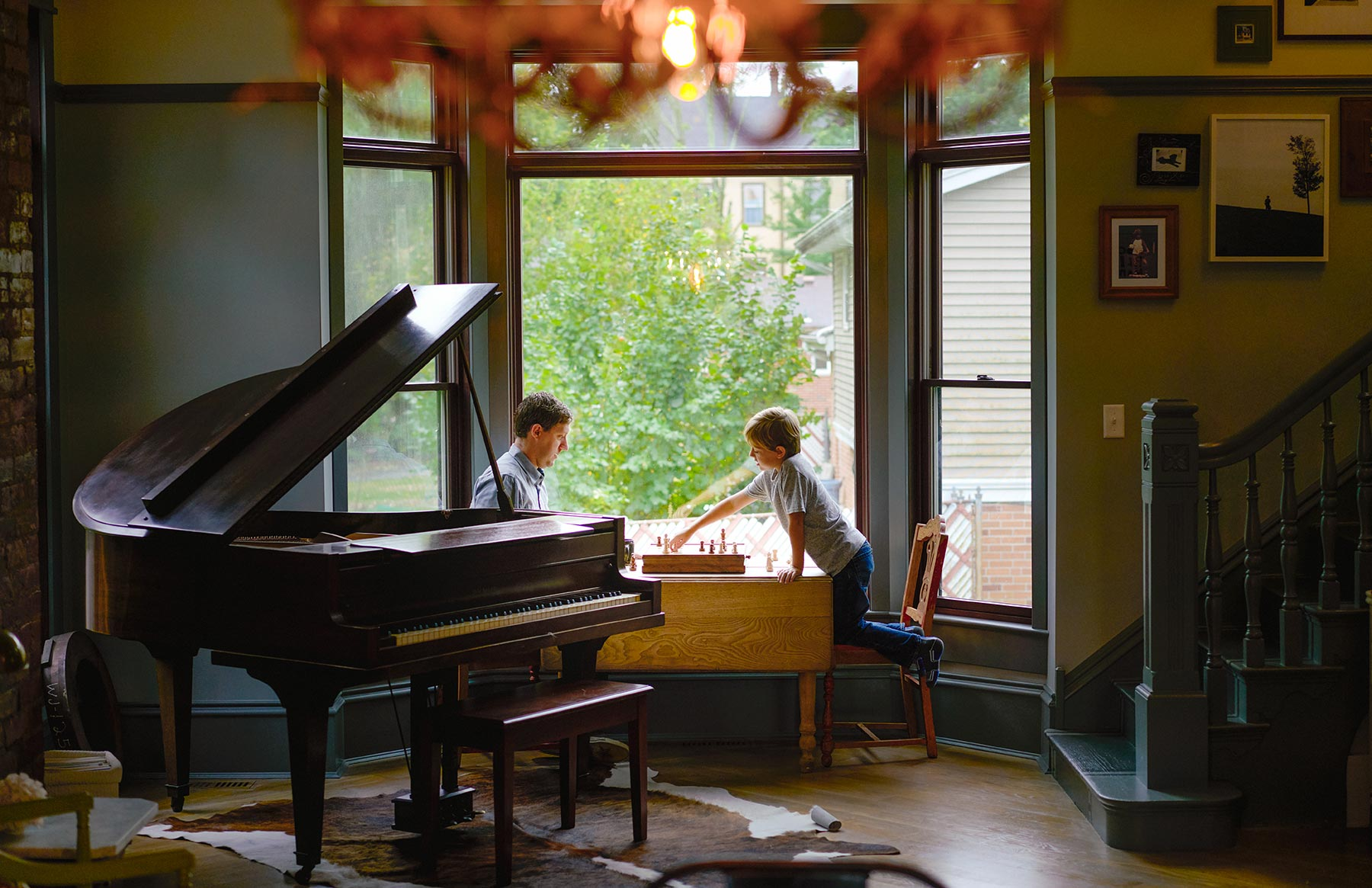 A-father-and-son-playing-chess-between-a-grand-piano-and-a-large-window-in-the-living-room-of-their-house