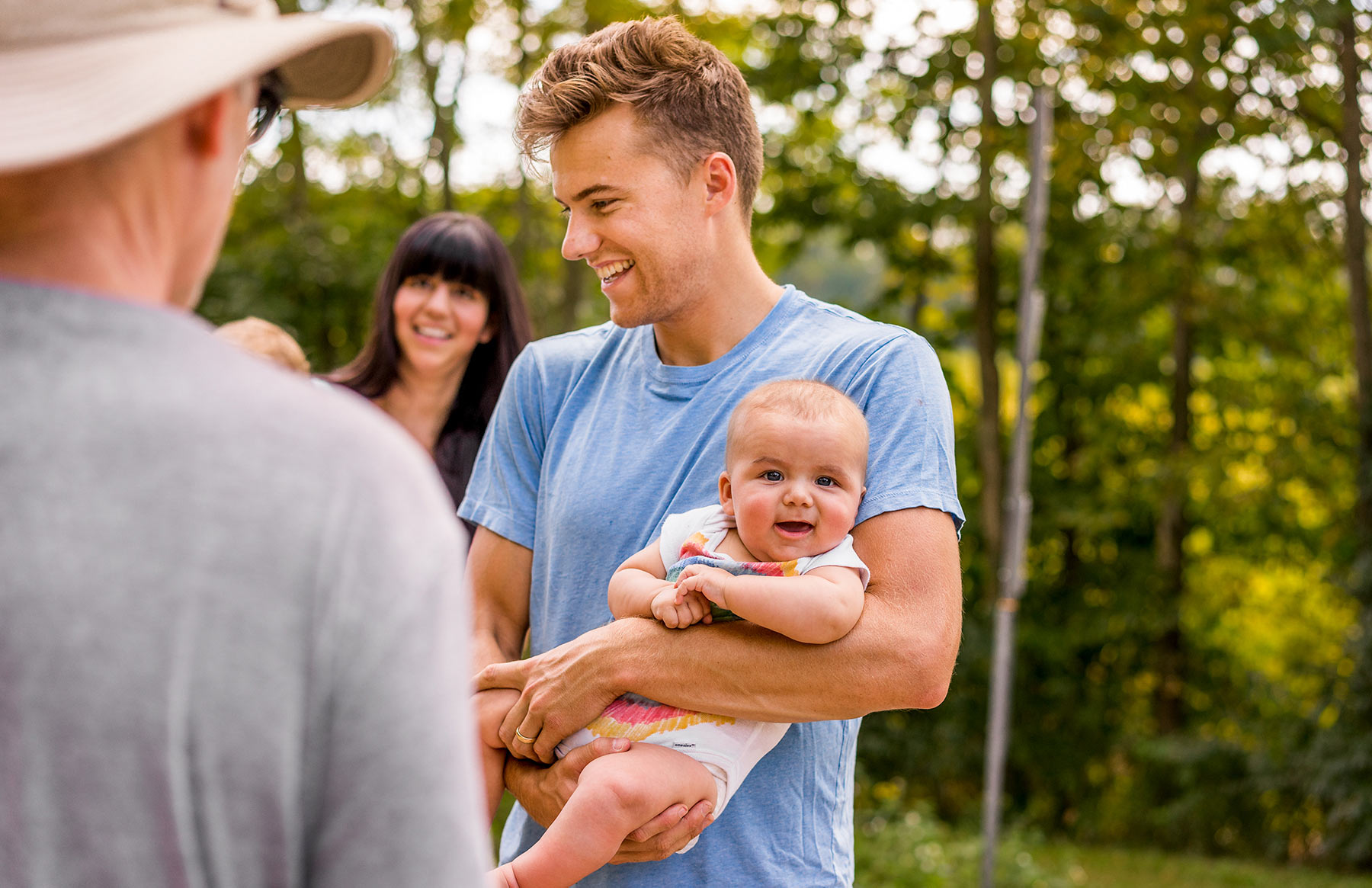 A-young-father-holding-his-baby-at-a-family-event