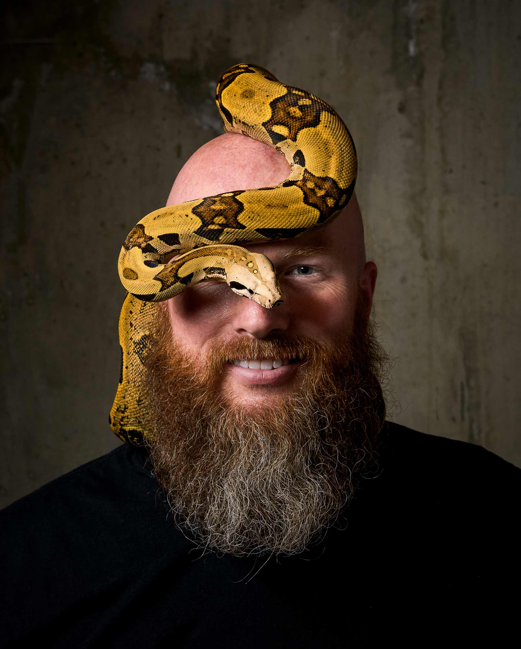 A-studio-portrait-of-a-man-with-a-yellow-and-black-snake-on-his-head