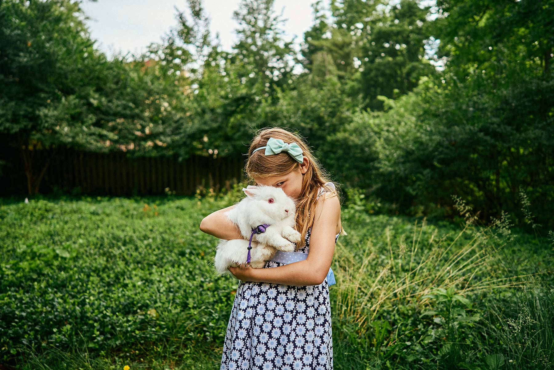 A-little-girl-hugging-her-white-rabbit-while-standing-in-a-green-yard
