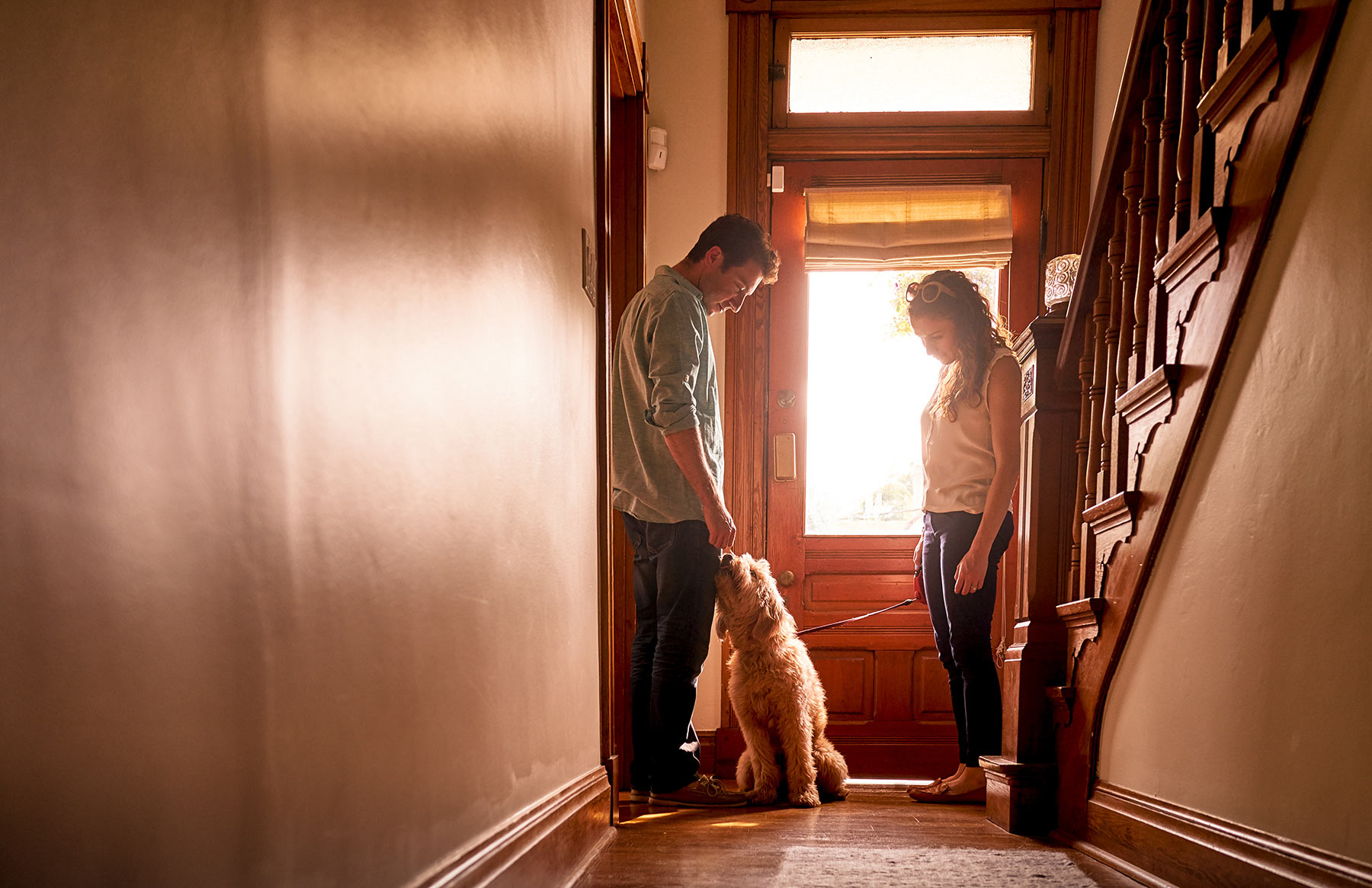 A-young-couple-greeting-their-dog-in-the-doorway-of-their-house