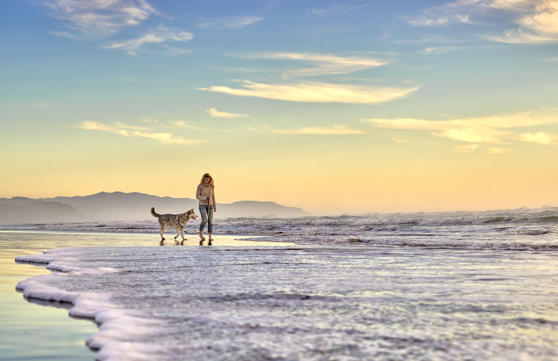 A-woman-and-her-Siberian-Husky-walking-along-the-edge-of-the-ocean
