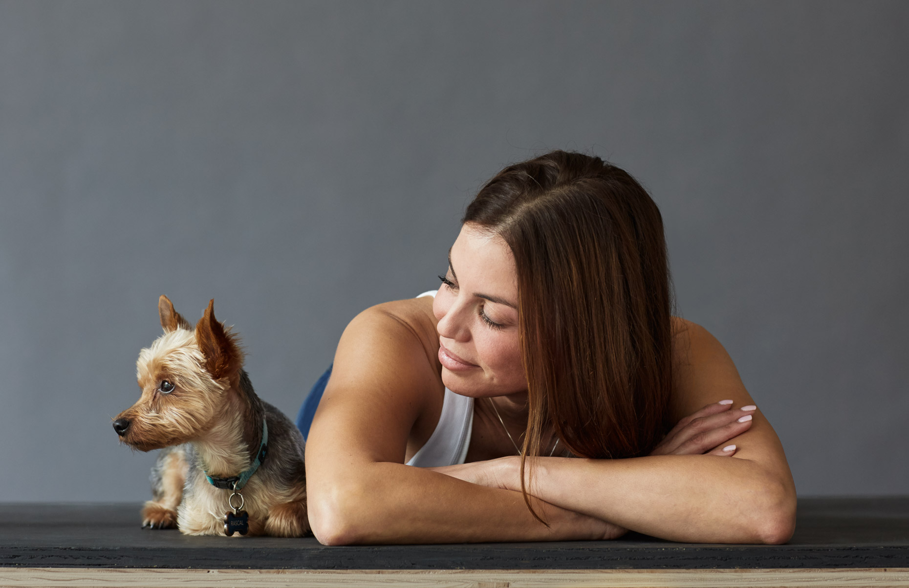 A-studio-portrait-of-a-woman-relaxing-with-her-dog-against-a-gray-background