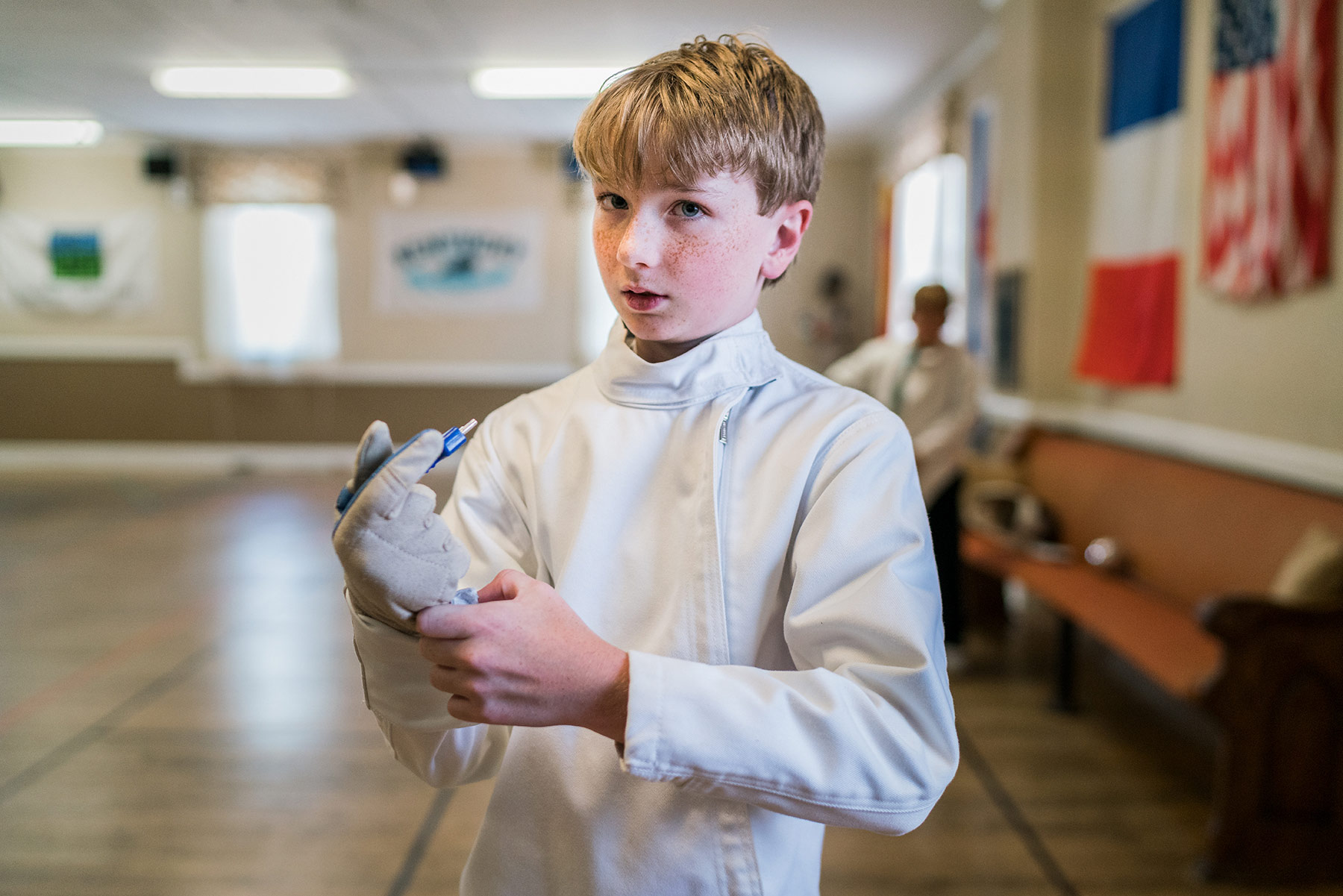 A-portrait-of-a-young-boy-wearing-a-fencing-outfit-standing-in-a-gymnasium