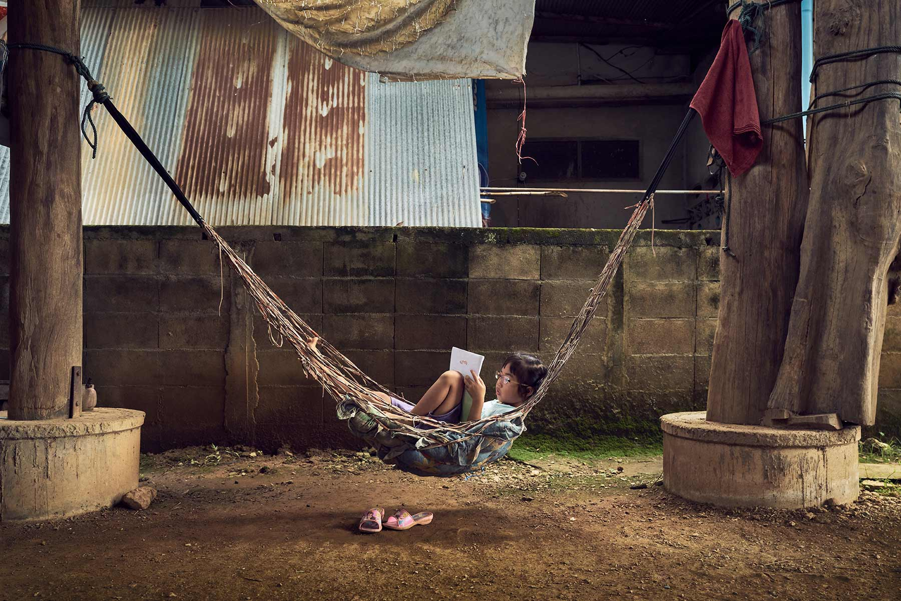 A-portrait-of-a-young-boy-relaxing-on-a-hammock-in-a-large-room-with-dirt-floors