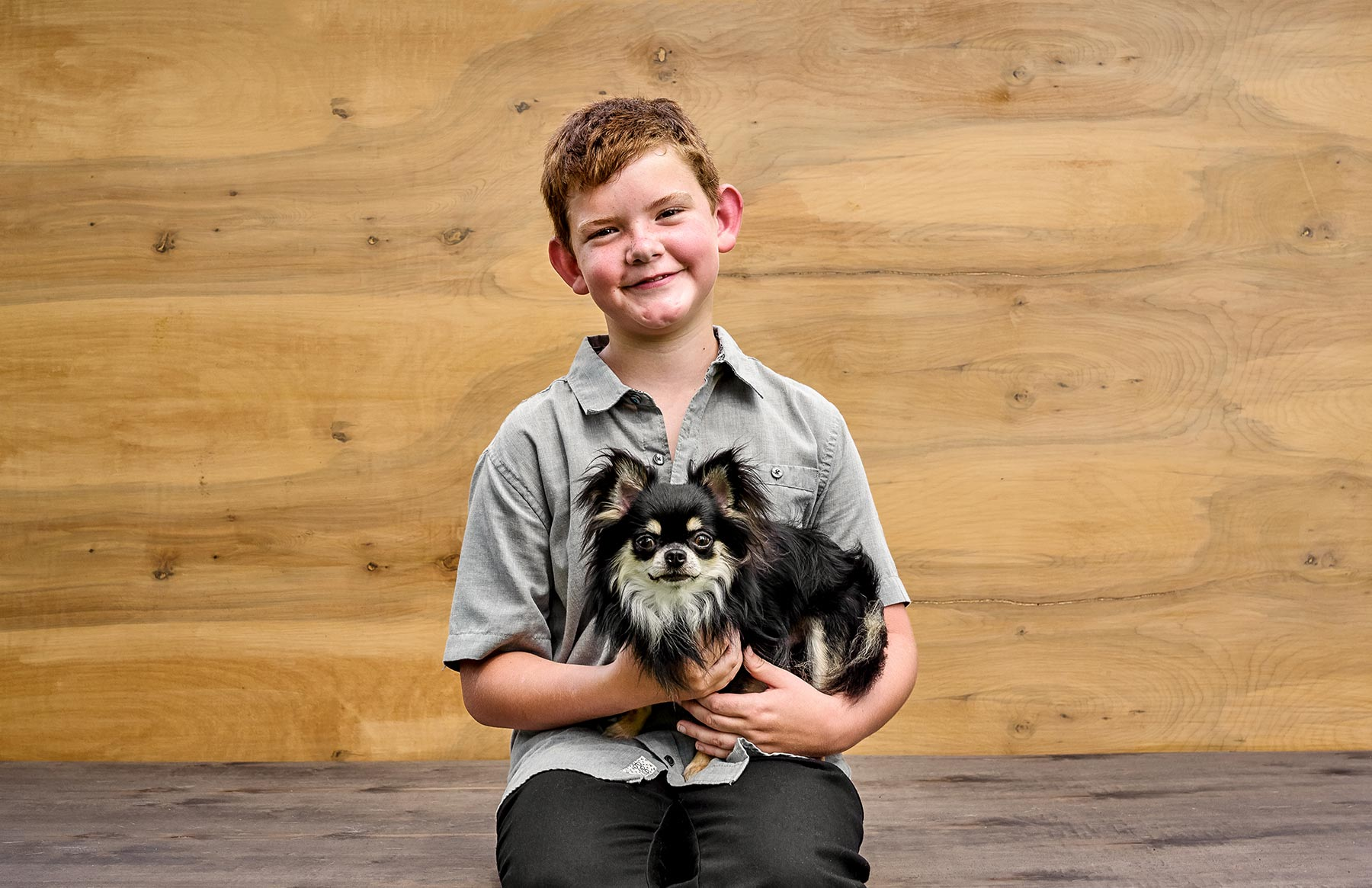 A-young-boy-holding-a-fluffy-black-and-white-dog-against-a-wooden-background