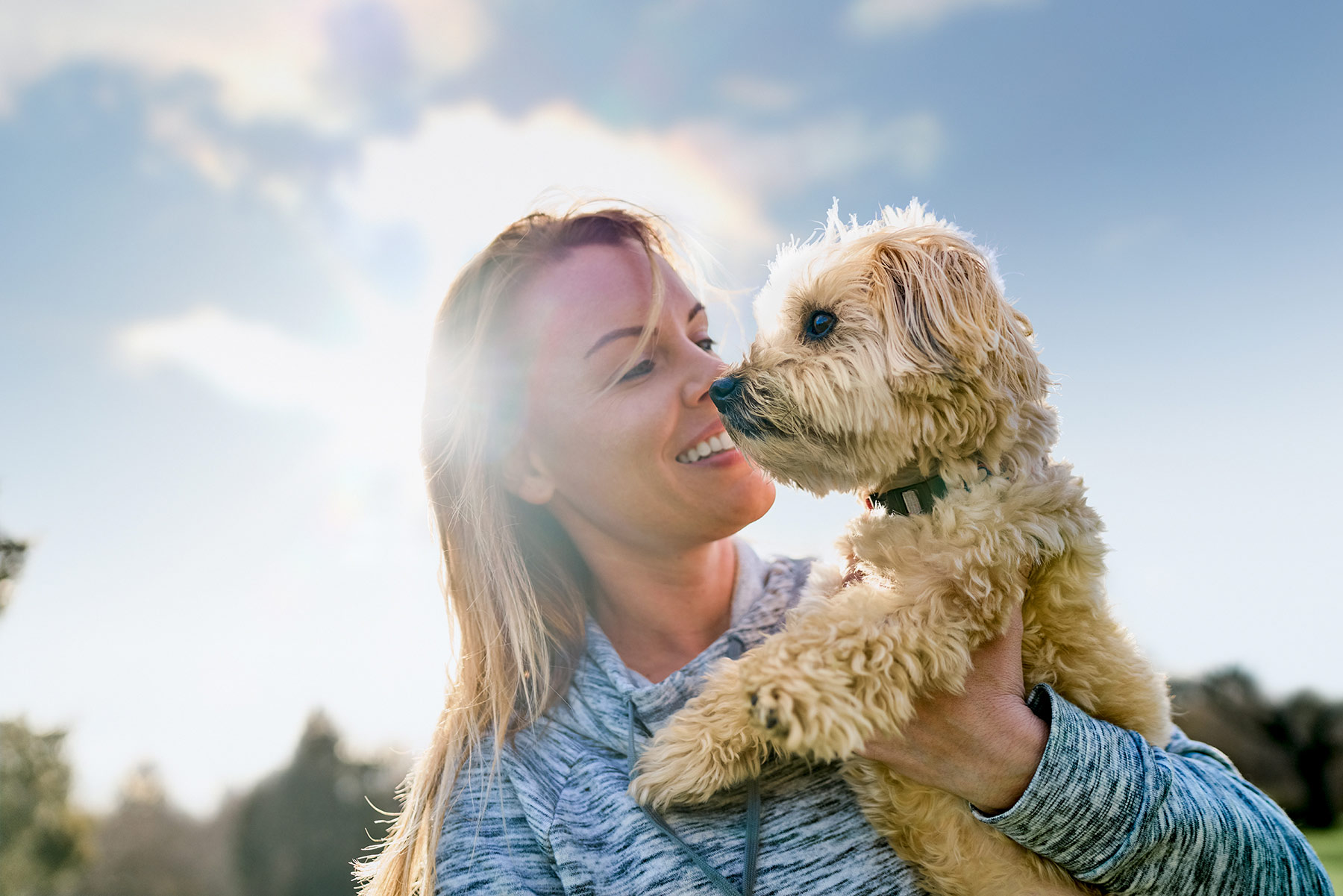 A-woman-holding-her-dog-against-a-sunlit-sky