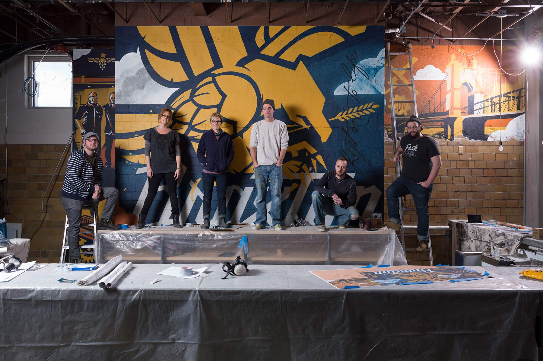 Six-young-adults-posed-in-front-of-a-wall-with-a-large-bird-logo-in-their-art-studio