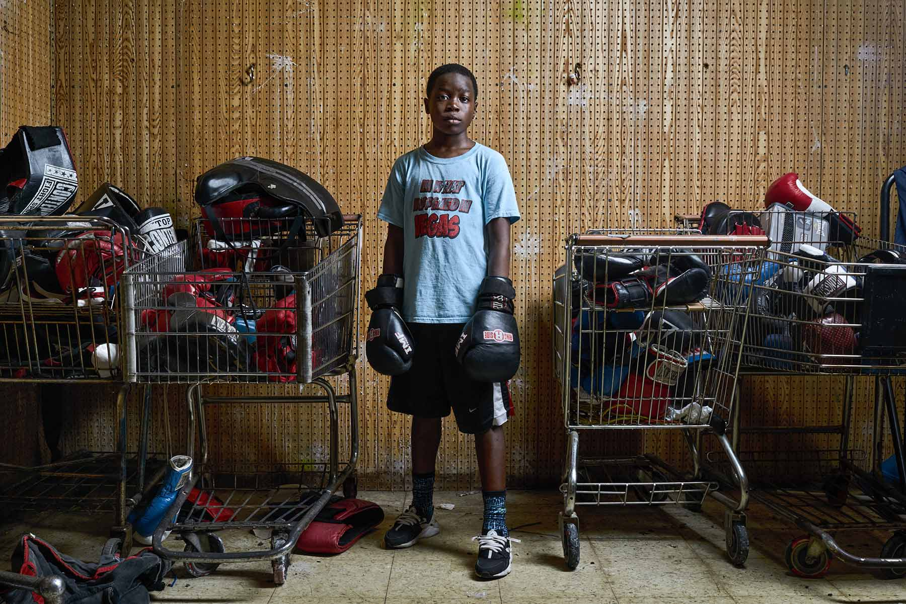 A-portrait-of-a-young-boy-wearing-boxing-gloves-standing-between-four-grocery-carts-full-of-sports-gear