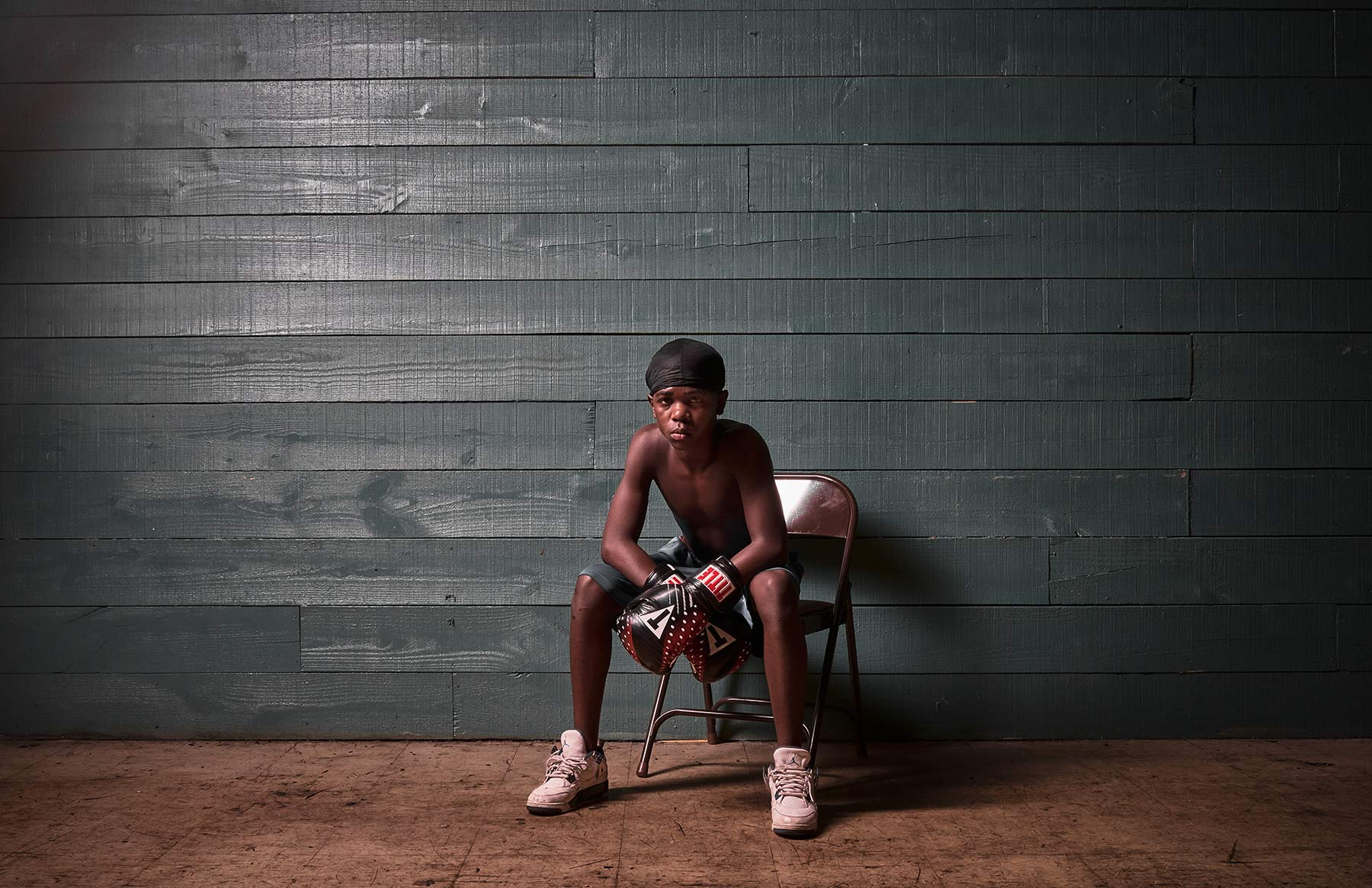 A-portrait-of-a-young-boy-wearing-boxing-gloves-sitting-in-a-chair-in-the-middle-of-an-empty-room-with-panneled-walls